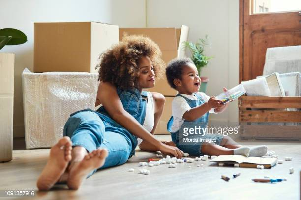 happy mother with daughter playing in new house - new home stock pictures, royalty-free photos & images