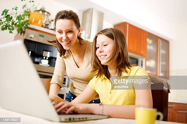 Happy Mother with Daughter using Laptop at home