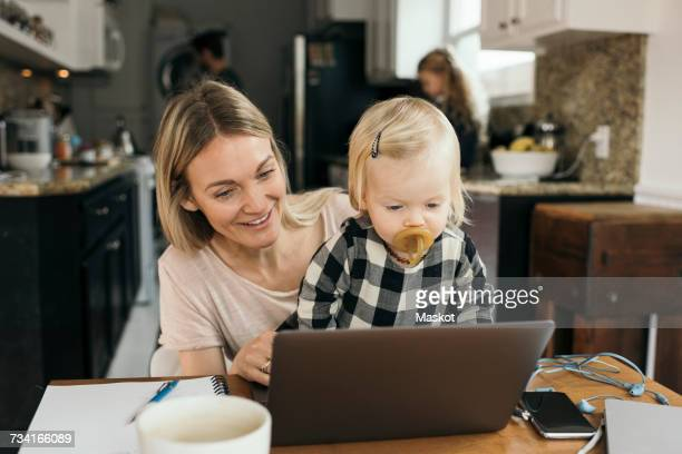 Happy mother with daughter using laptop with family in background at home