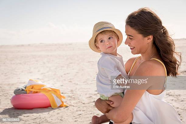 Happy mother with her little son enjoying on beach