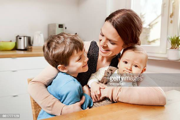 Happy mother with her little sons in the kitchen