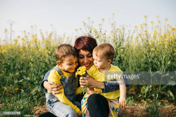 Happy mother with little son and daughter in nature
