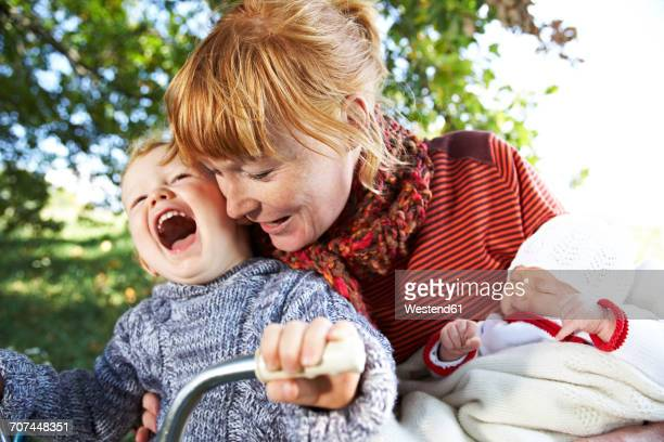 Happy mother with son and baby in the nature