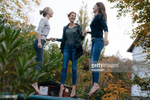 happy mother with two teenage girls jumping on trampoline in garden in autumn - ragazzine scalze foto e immagini stock