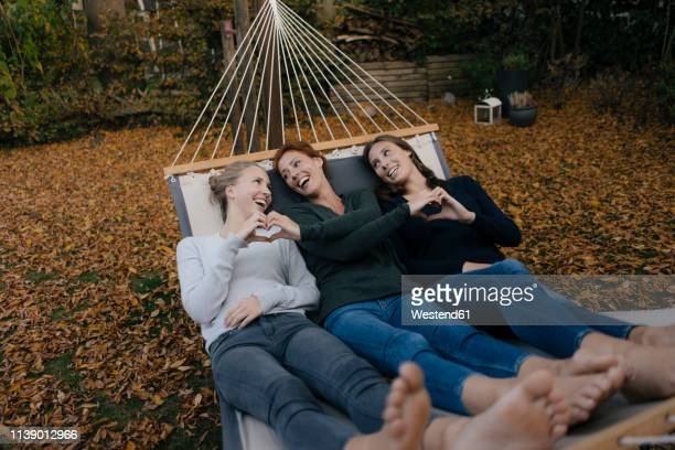 happy mother with two teenage girls lying in hammock in garden in autumn - hot teen stock pictures, royalty-free photos & images