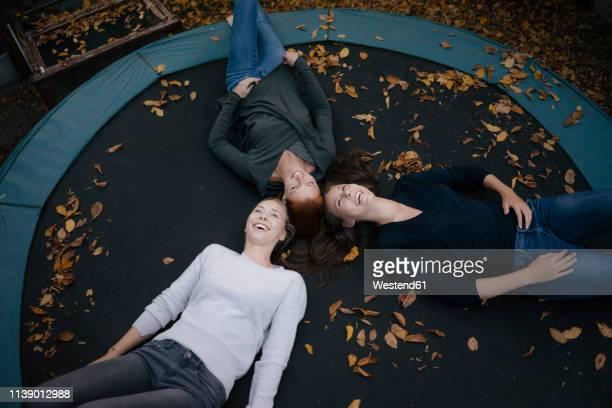 happy mother with two teenage girls lying on trampoline in autumn - einfaches leben stock-fotos und bilder