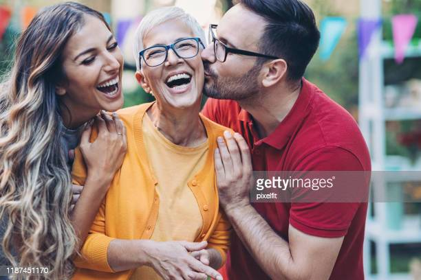 gelukkige moeder-in-law met jong gezin - volwassen nageslacht stockfoto's en -beelden