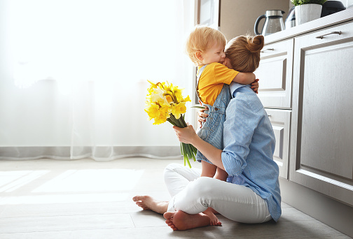 happy mother's day! baby son gives flowersfor  mother on holiday 941590958