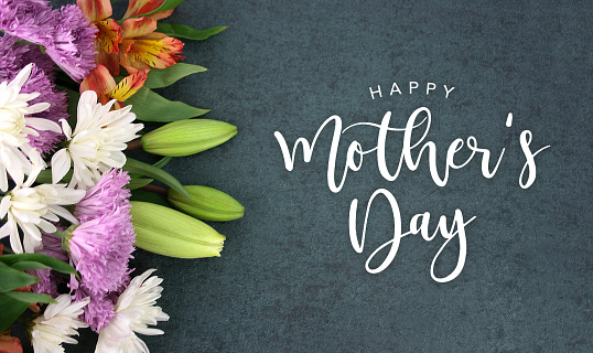 Happy Mother's Day calligraphy holiday script over dark blackboard background with beautiful colorful white, pink, orange, purple and green flower blossom bouquet 940292520
