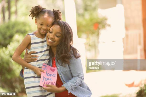 happy mother's day. girl gives card to mother. - mother's day stock pictures, royalty-free photos & images