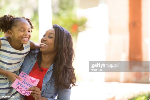 happy mother's day. girl gives card to mother. - black mothers day stock pictures, royalty-free photos & images