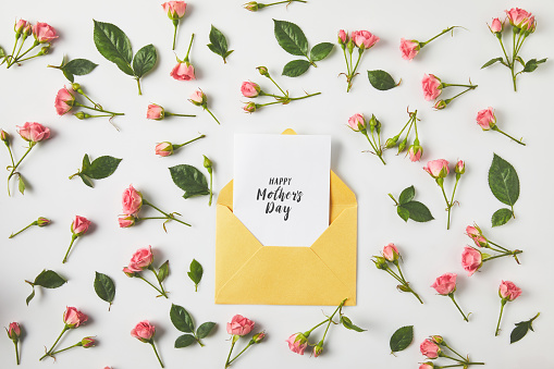happy mothers day greeting card in envelope and beautiful pink roses and green leaves on grey 944034496