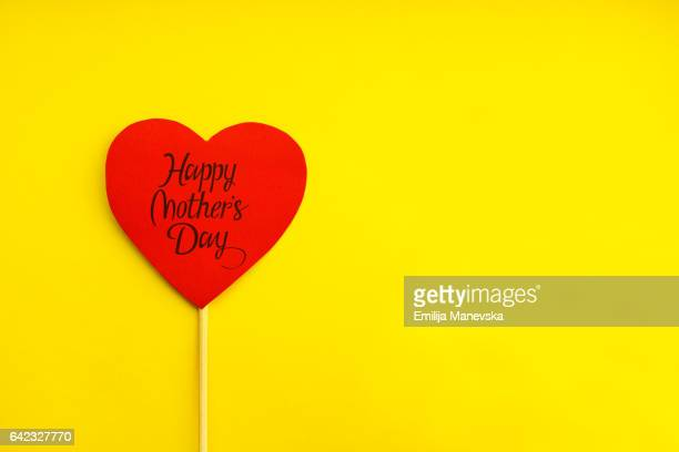Happy Mother's Day. Red paper heart on yellow background
