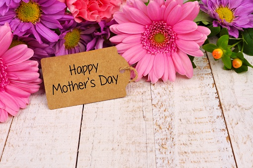 Happy Mothers Day tag close up with flowers over white wood 938848046