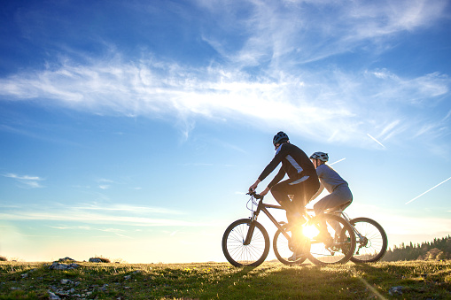 Happy mountain bike couple outdoors have fun together on a summer afternoon sunset 959028830