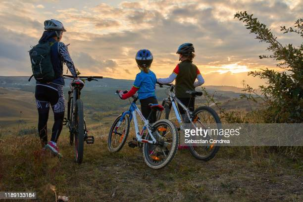 happy mountain bike family,  outdoors have fun together on a summer afternoon sunset, cycling girls activity - small group of people stock pictures, royalty-free photos & images