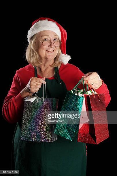 felice mamma natale guardando la telecamera con le borse omaggio - mamma natale foto e immagini stock