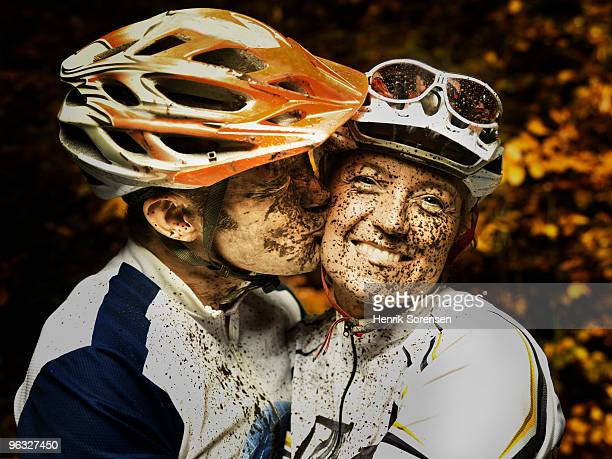 Happy mud covered mountain bikers kissing