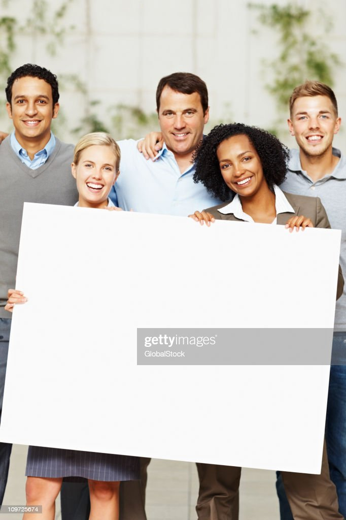 Happy multi ethnic business group holding a billboard : Stockfoto