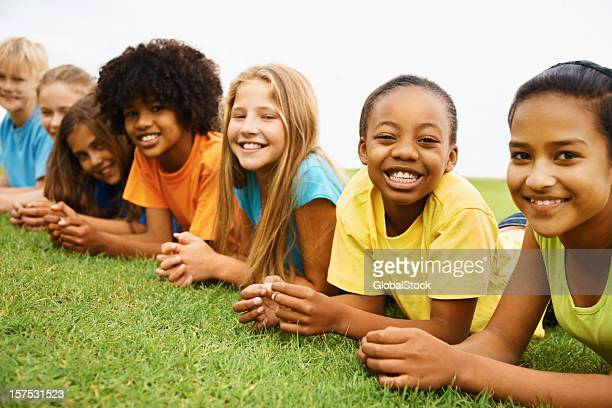 Happy multi ethnic kids lying on grass