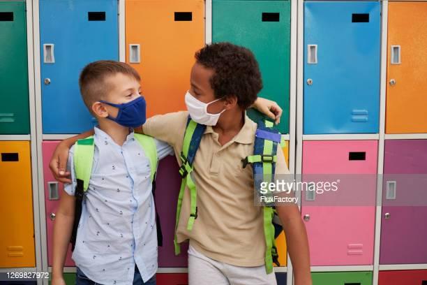 学校で保護フェイスマスクを着用しながら抱き合う幸せな多民族男性の友人 - 反人種差別 ストックフォトと画像