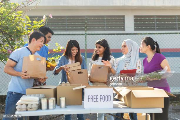 happy multi ethnic volunteers at food bank preparing for charitable food drive - participant stock pictures, royalty-free photos & images