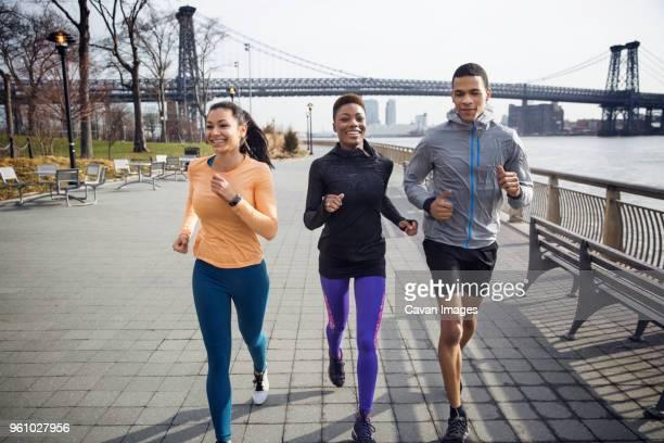 Happy multi-ethnic athletes running on footpath with Williamsburg Bridge in background