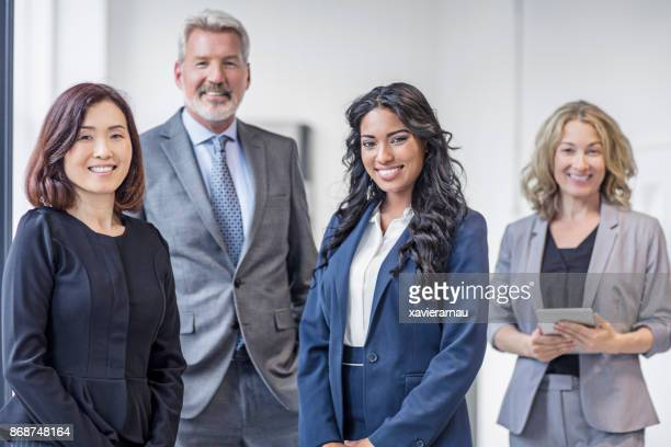 happy multi-ethnic business group smiling in the office - four people stock pictures, royalty-free photos & images