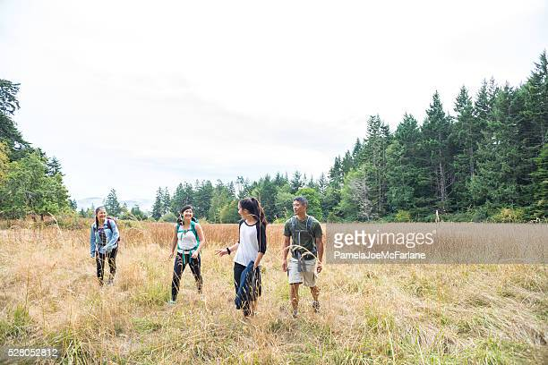 Happy Multi-Ethnic Family Hiking Through Grassy Meadow Surrounded by Forest