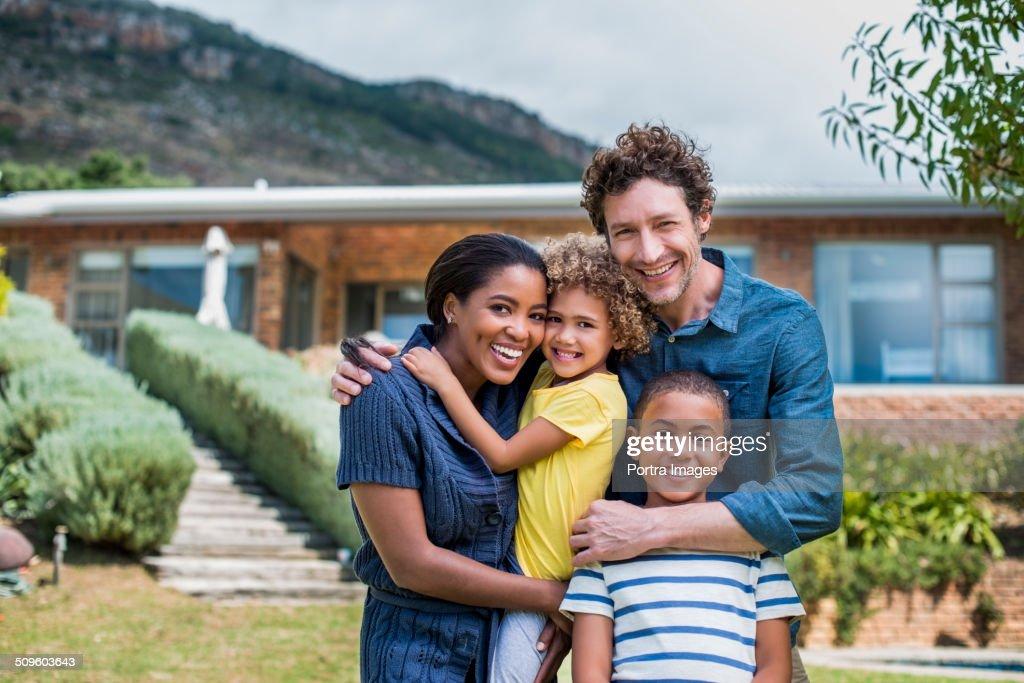 Happy multi-ethnic family outside house : Stock Photo