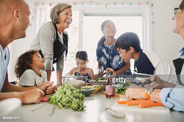 Happy multi-ethnic family preparing Asian food at kitchen