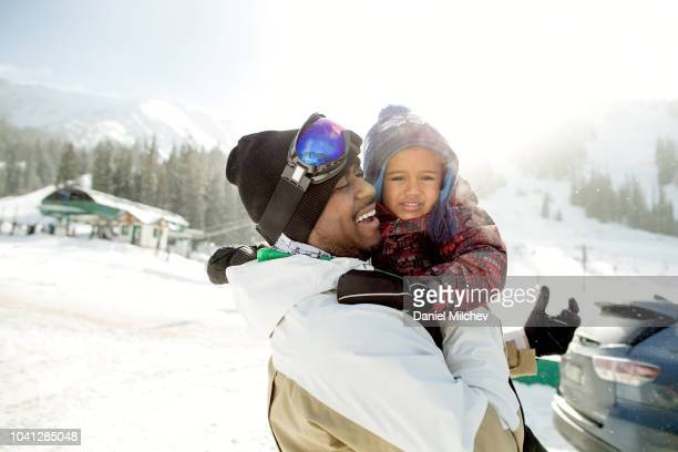 happy multi-ethnic father and son at a ski resort getting ready to go skiing. - スキー旅行 ストックフォトと画像