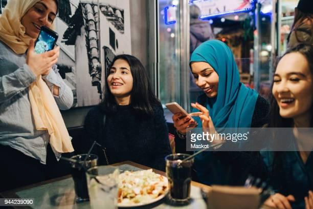 Happy multi-ethnic female friends enjoying at cafe