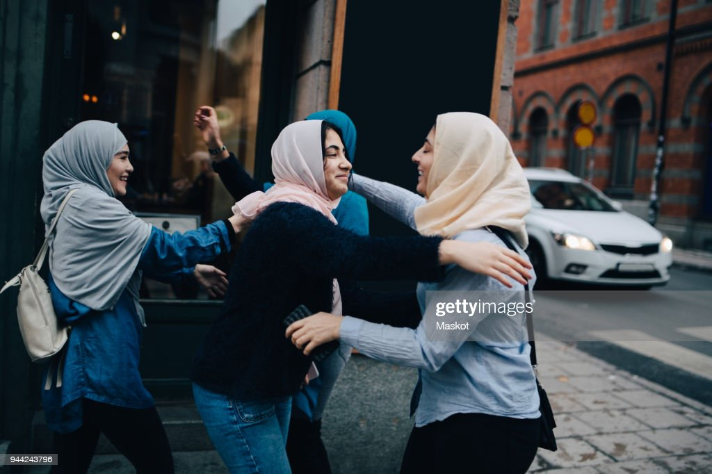 Happy multi-ethnic female friends greeting on sidewalk in city : Stock Photo