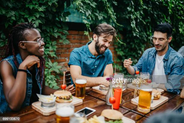 Happy multi-ethnic friends at the pub are having a lunch