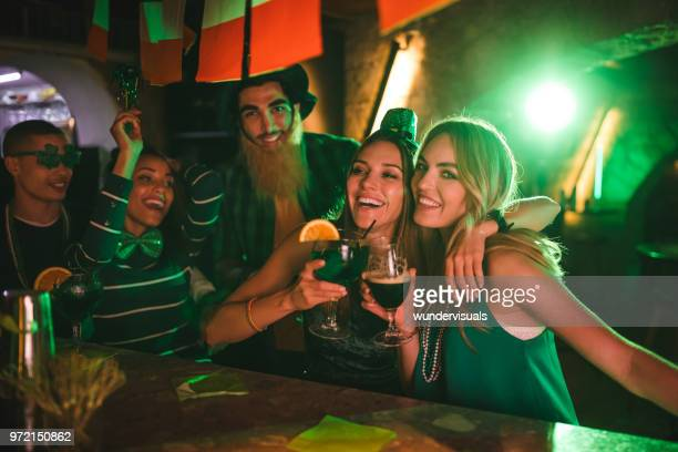 happy multi-ethnic friends in costumes partying on saint patrick's day - st patricks stock pictures, royalty-free photos & images