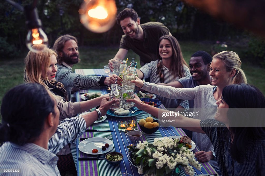 Happy multi-ethnic friends toasting drinks at dinner table in yard : Stock Photo