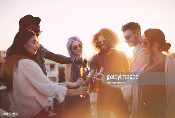 happy multi-ethnic friends toasting with drinks at summer terrace party - roof stock photos and pictures