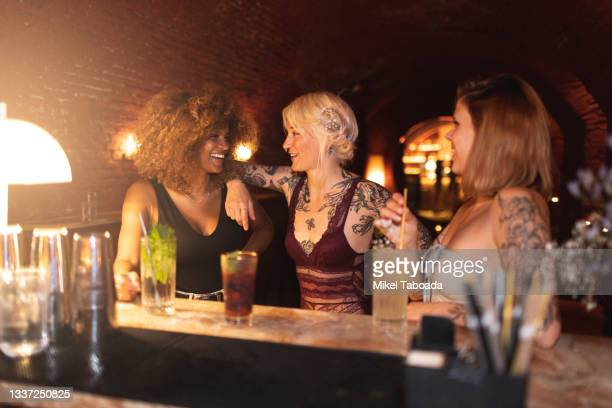 happy multiethnic girlfriends talking against cocktails in bar - friendly match stock pictures, royalty-free photos & images