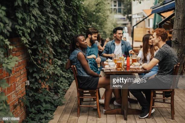 Feliz grupo multiétnico de gente sentada en el restaurante de comida rápida