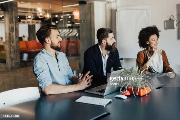 happy multi-ethnic group of people sitting by the table in the briefing room - digital marketing stock photos and pictures