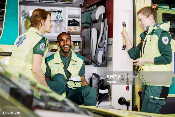 happy multi-ethnic paramedics talking while sitting in ambulance at parking lot - rescue worker stock pictures, royalty-free photos & images