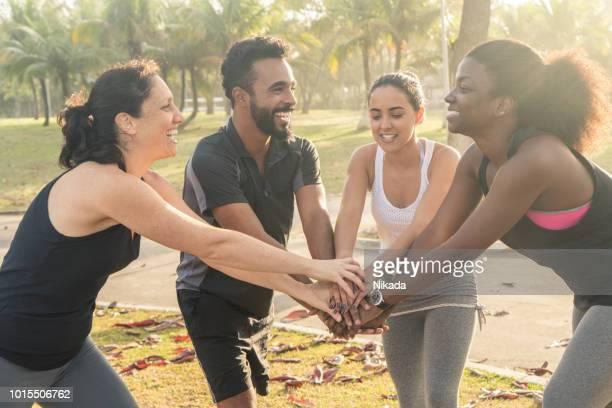 Glücklich multiethnischen sportliche Freunde Stapeln Hände im park