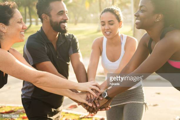happy multi-ethnic sporty friends stacking hands at park - brazilian men stock photos and pictures