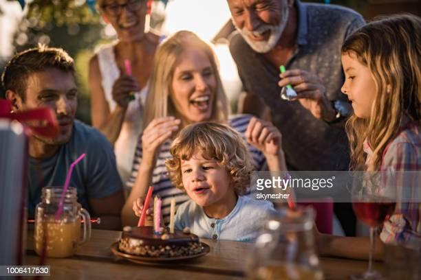 família de várias gerações feliz comemorando o aniversário do filho ao ar livre. - birthday candles - fotografias e filmes do acervo