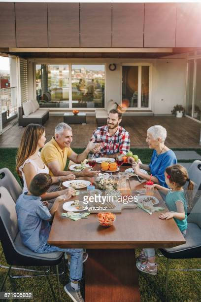 happy multi-generation family communicating during lunch on a penthouse balcony. - penthouse girls stock pictures, royalty-free photos & images