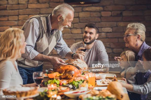 happy multi-generation family communicating while enjoying in thanksgiving dinner. - family dinner stock photos and pictures