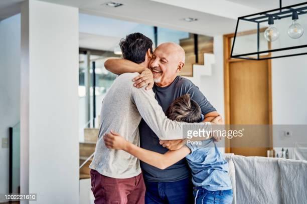 glad flergenerationsfamilj som omfamnar hemma - son bildbanksfoton och bilder