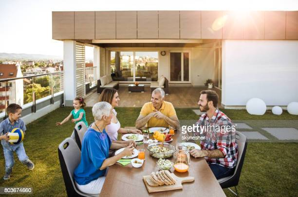 happy multi-generation family enjoying during a meal on the balcony. - penthouse girls stock pictures, royalty-free photos & images