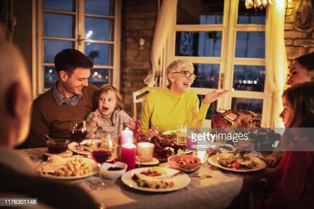 gelukkige multi-generatie familie genieten in gesprek tijdens thanksgiving diner aan de eettafel. - evening meal stockfoto's en -beelden